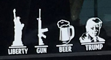 """Close up photo of decal showing an image of the Statue of Liberty, an automatic rifle, a beer mug, and Donald J. Trump along with the words """"Liberty"""" """"Gun"""" """"Beer"""" and """"Trump."""""""